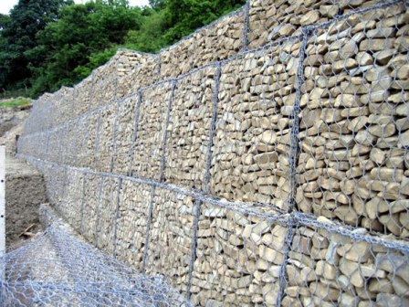Gabions wall support of hexagonal mesh box cells filled with stones